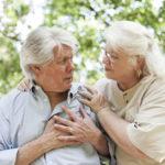 A senior man experiencing chest pain.  A senior woman comforts him.