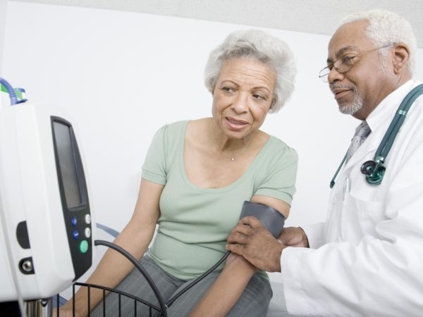 Male doctor checking patient's blood pressure while looking at machine at clinic