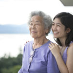 Asian Grandmother and Eurasian granddaughter with park, water and mountains in background.