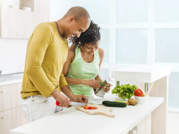 Smiling African American couple preparing food together in the kitchen.