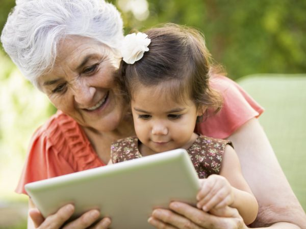 A grandmother showing tablet to her grandchild.