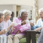 A group of four multi-ethnic seniors sitting together on patio furniture outdoors, talking and smiling, drinking tea or coffee. One of the men and the African American senior woman are toasting with their cups. They are in retirement, relaxed and enjoying spending time with friends.