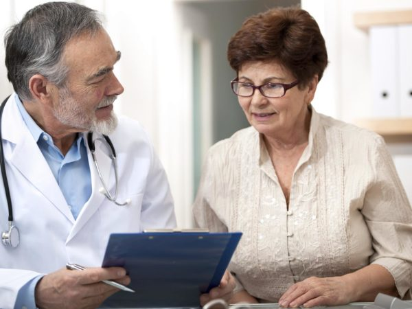 Doctor discussing treatment with senior female patient