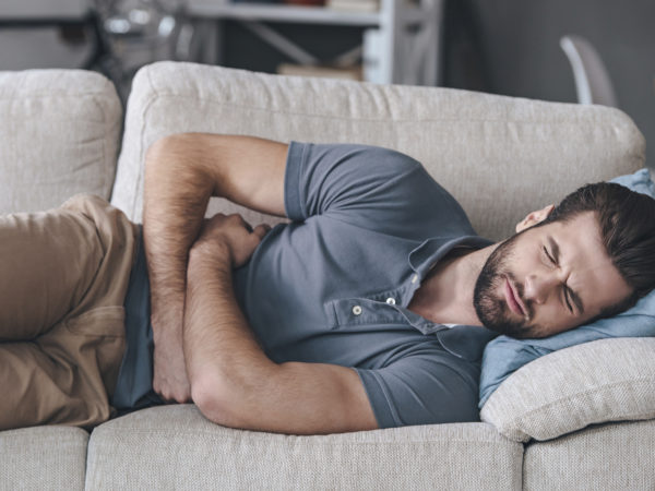 Frustrated handsome young man hugging his belly and keeping eyes closed while lying on the couch at home