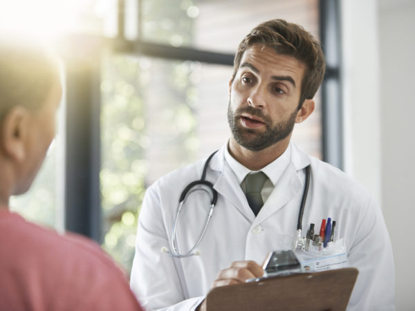 Shot of a male doctor talking with a patient in a hospital lobby