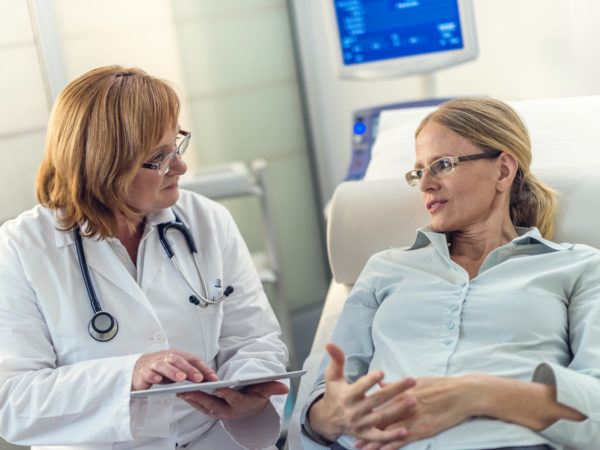 Patient on the bed telling her doctor about the problems she is having while the doctor is listening.