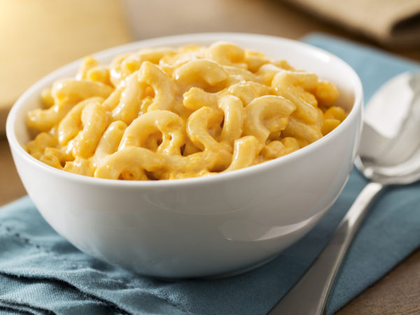 A white bowl of the best baked homemade macaroni and cheese on a table with a blue napkin.  The recipe is made with elbow pasta and cheddar cheese.  The shot is vertical and has selective focus.  Macaroni and cheese is a American comfort food or soul food.