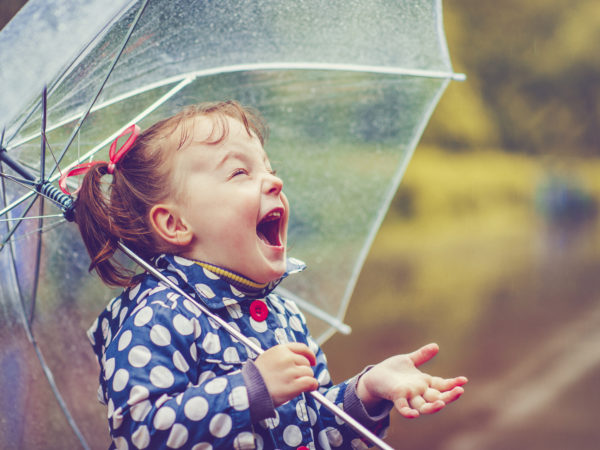 Little girl with umbrella in autumn