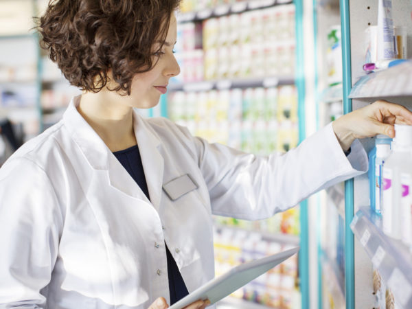 Young pharmacist with a digital tablet in drug store checking medicines on the shelf