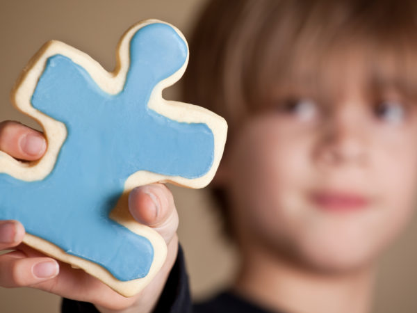 """A 9 year old boy holding out a blue iced puzzle piece shaped sugar cookie.  Shallow DOF, focus on cookie only.April is Autism Awareness month. Colorful puzzle pieces are often used to represent Autism awareness.  1 in 88 children in the USA are diagnosed with an ASD (Autism Spectrum Disorder)."""