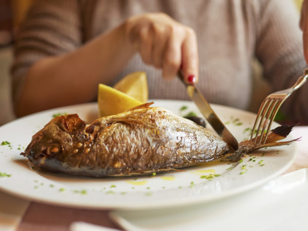 horizontal shot of young woman hands preparing to eat her lunch, fish and lemon in plate.