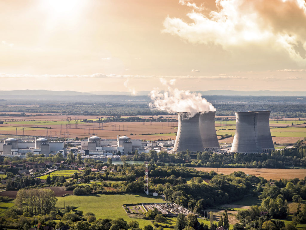 Horizontal composition photography of french nuclear power station with  four steaming cooling towers in countryside plain