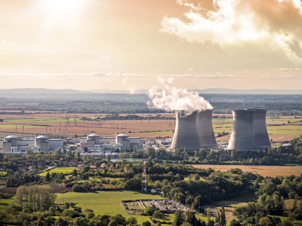 Horizontal composition photography of french nuclear power station with four steaming cooling towers in countryside plain with smoke cloud (water condensation). Image taken from high angle view, aerial view, in Bugey, in Ain on the border of Isere department, Rhone-Alpes region in France (Europe). The nuclear power station is located in the middle of a plain landscape in France, near Lyon city. This picture was taken during a bright orange sunset in autumn season with green and brown meadow and field.