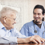 An in home healthcare nurse smiling with his 90 year old patient as they go over his chart.
