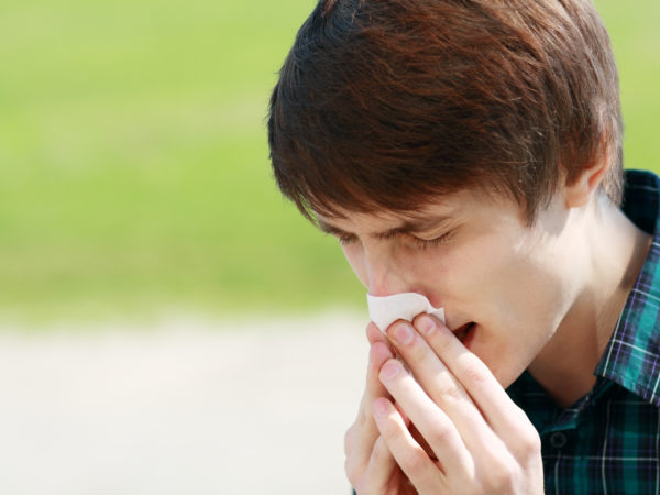 Young man sneezing outdoor and blowing his nose because he has allergies.