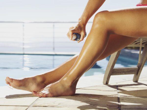 Woman applying suntan spray onto her legs. Female sitting on recliner chair by the swimming pool sunbathing.