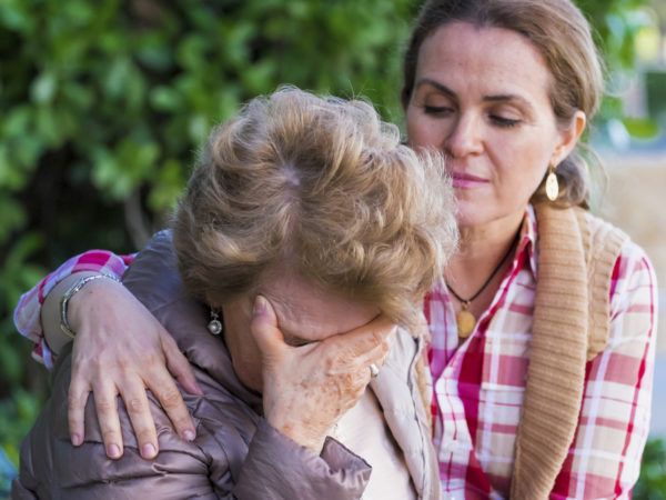 Senior woman with her hands on her head looking down sitting in a park bench with her daughter consoling her