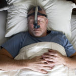 Photo of a man sleeping while wearing a CPAP mask.
