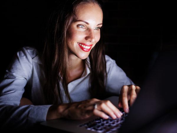 Beautiful caucasian women in white shirt sitting in dakness and typing on laptop with smile