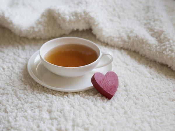 White teacup on white textile vintage texture