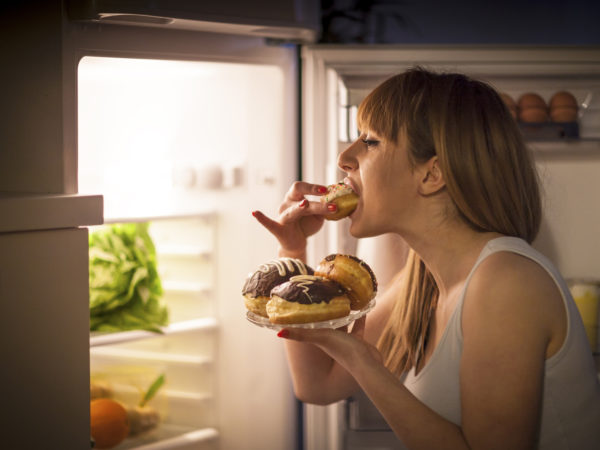 Close up image of a young woman with eating disorder, having a midnight snack - eating donuts, in front of the refrigerator.