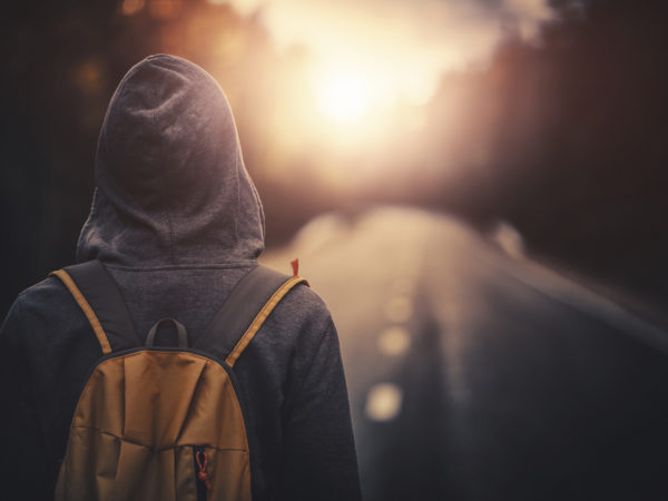 Traveler with backpack walking forward alone at sunset. Stock photo.