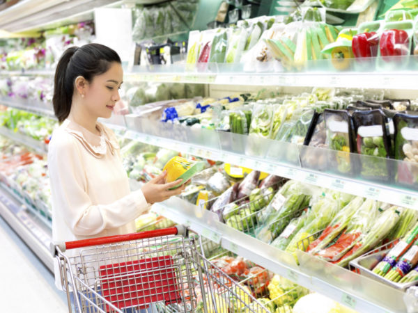 asian woman attentively considers vegetables in shop