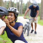 Caring young mother helping daughter put on helmet with father in background - Outdoors in country side