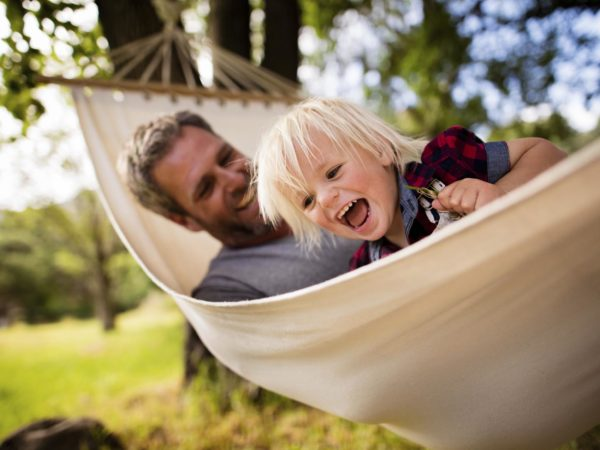 Lovely modern dad enjoys the outdoors playing with his son on a white hammock