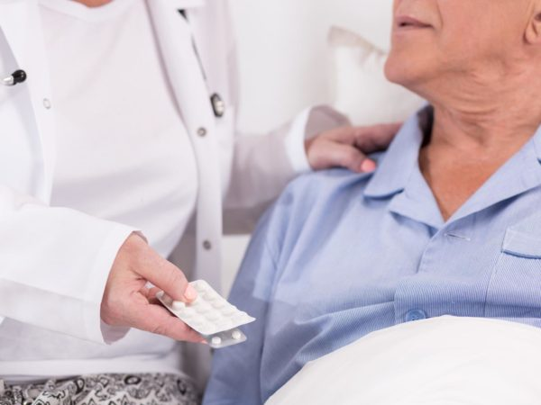 Close up of nurse giving medicines to ill patient
