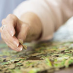 Close up of senior woman's hand putting together puzzle