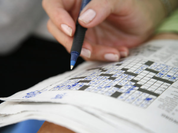 Working on a crossword puzzle.