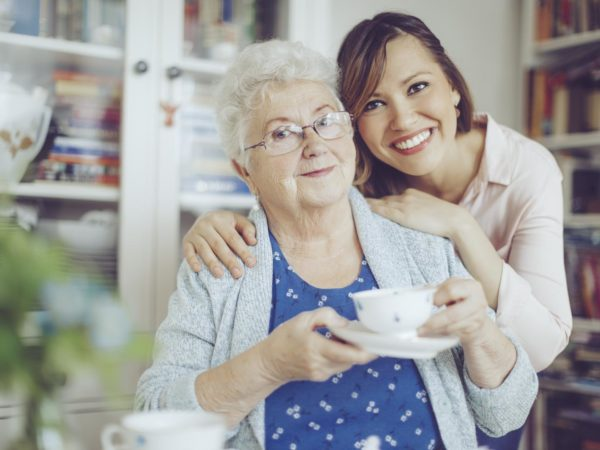 Social worker is visiting a senior woman in her own apartment. They are celebrating the elderly lady's birthday. The kind nurse is hugging the senior woman over her shoulder.