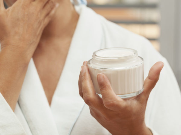 Close up portrait of mature woman applying facial cream. She is wearing white bathrobe. Selective focus. Face is not visible.