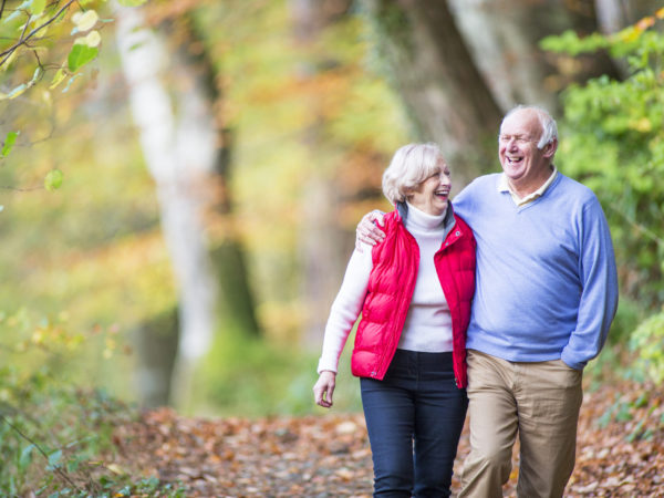 A happy senior couple take a stroll through the woods together.