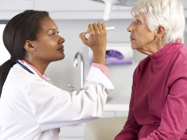 Female Doctor Examining Senior Female Patient's Eyes