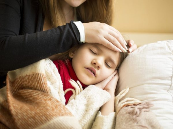 Closeup photo of caring mother holding head on sick daughter forehead