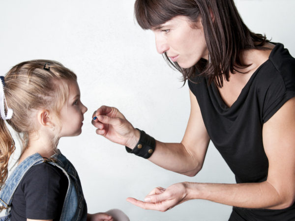 Mom giving medicine to little girl – I