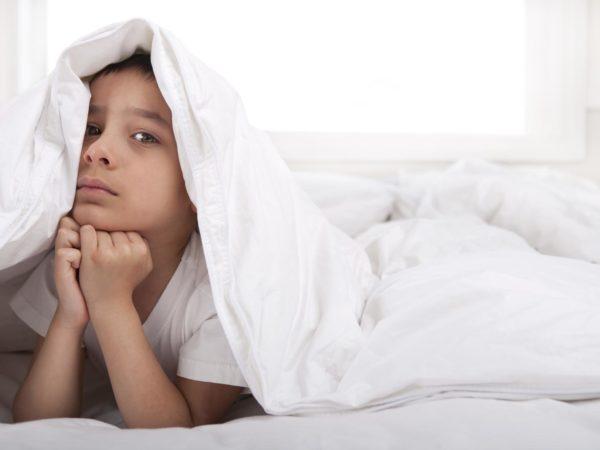 Sad little boy laying under blanket