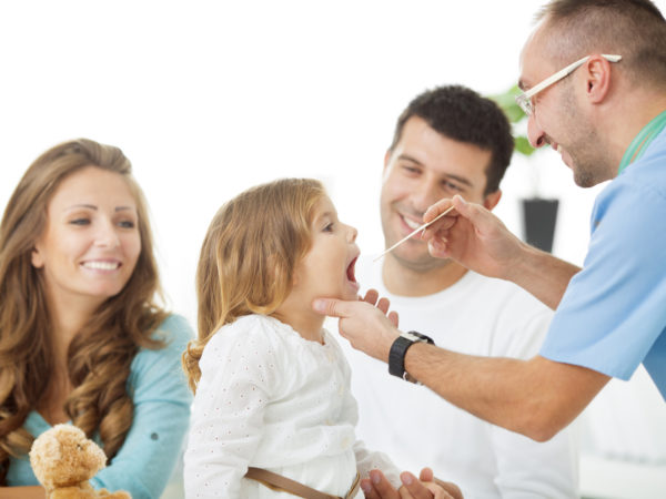 Cheerful family with little girl at doctors office. Doctor examine girls for sore throat. Father holding little girl during examining.