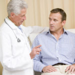 Doctor giving middle-aged man checkup in exam room