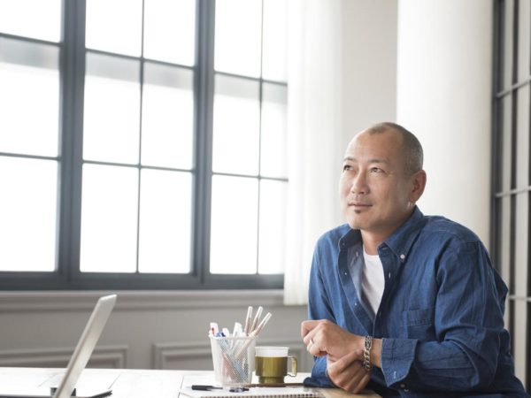 Thoughtful Japanese man looking for inspiration and creativity. Pensive Asian businessman looking away from desk