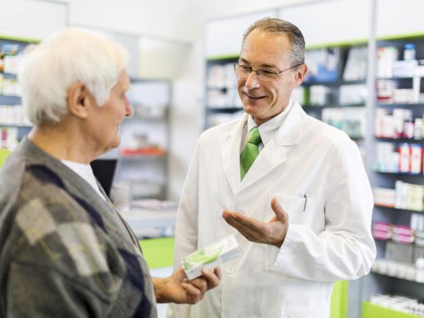 Mature pharmacist talking to senior man in a pharmacy.