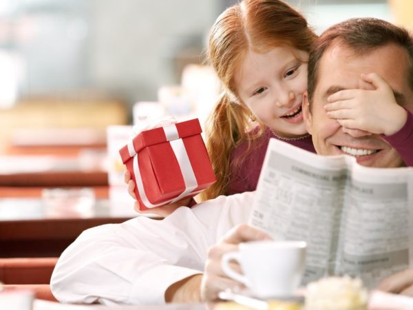 Little daughter giving a gift box to her father