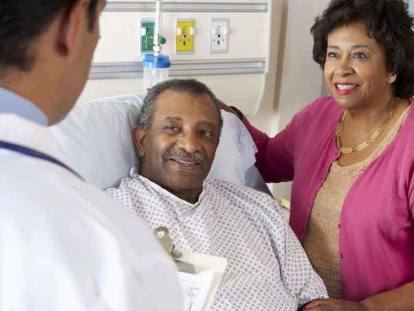 Male Doctor Talking To Senior Couple On Hospital Ward