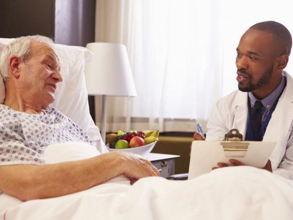 Doctor Talking To Senior Male Patient In Hospital Bed