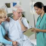 Mature Hispanic doctor or nurse talks with senior patient and his wife about his test results. The man and his wife are sad and he has his hand on his face. They are holding hands. He is connected to iv drip. The nurse or doctor is wearing scrubs and is holding the test results attached to his medcal chart. The man is wearing a hospital gown.