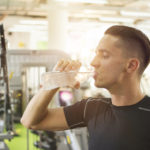 Handsome young man drinking water from a bottle and taking a break from exercising in a gym.