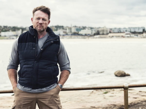 Color portrait of a mature, rugged, tough Australian man with Bondi Beach of Sydney in the background. 16x9 letterbox format with copy space on right.