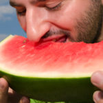 Young man eating watermelon in the Nature